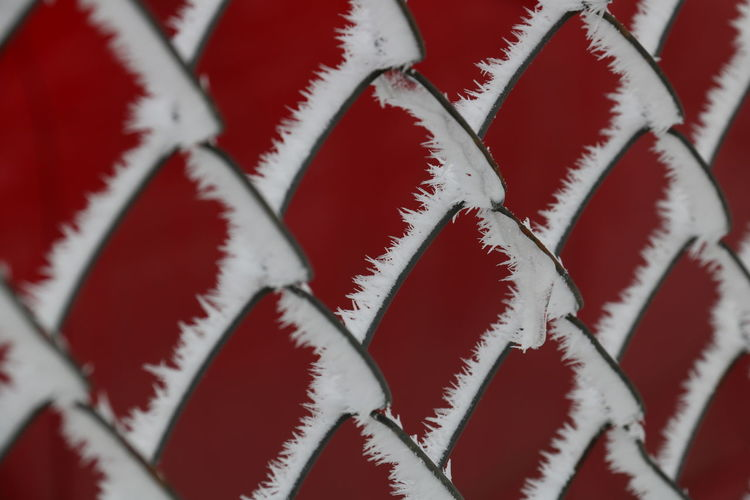 Full Frame Shot Of Frost On Chainlink Fence Against Red Wall