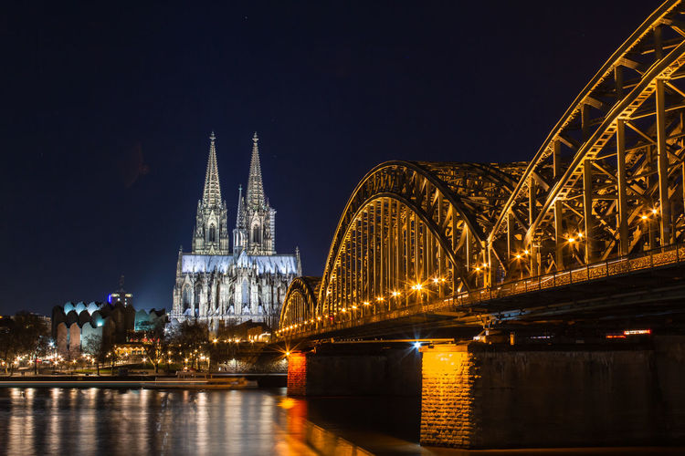 Cologne skyline with Cologne Cathedral and Hohenzollern bridge at night Cologne Cologne Cathedral Cathedral Architecture Built Structure Night Illuminated Bridge Building Exterior Connection Water Bridge - Man Made Structure Travel Destinations Sky River City Reflection No People Nature Transportation Building Outdoors Arch Bridge Spire