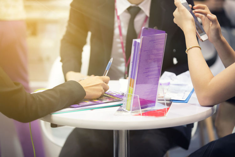 Midsection of businesspeople brainstorming on desk at office