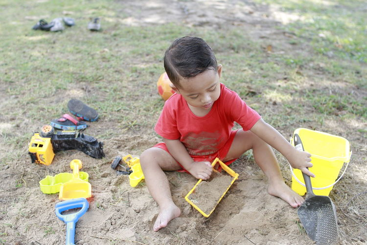 High angle view of boy playing with toys on sand