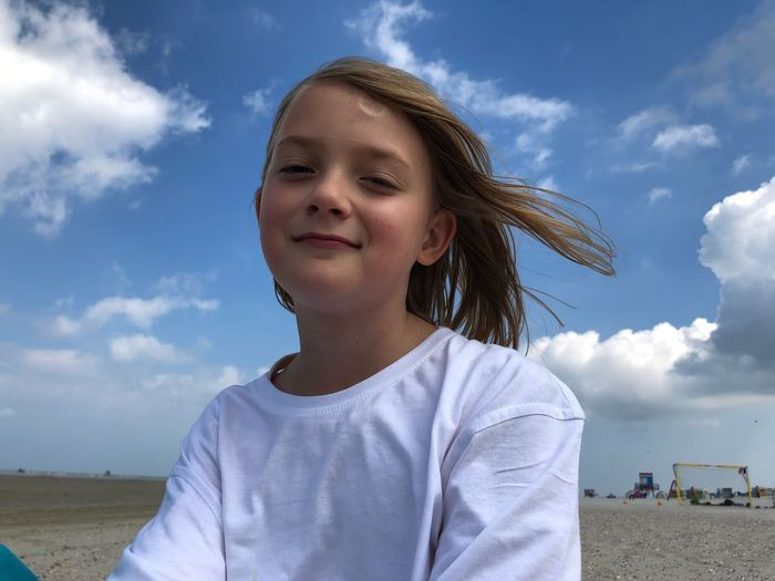 Portrait of smiling girl at beach against sky