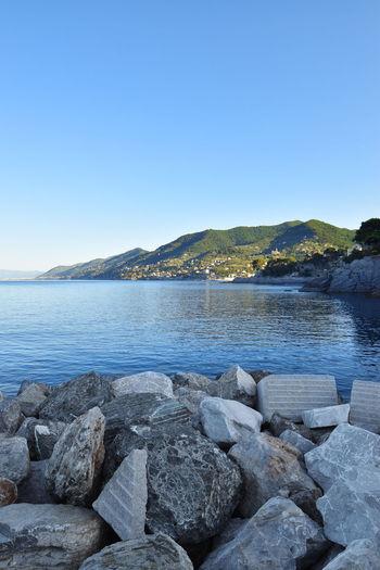 Rocks by sea against clear blue sky