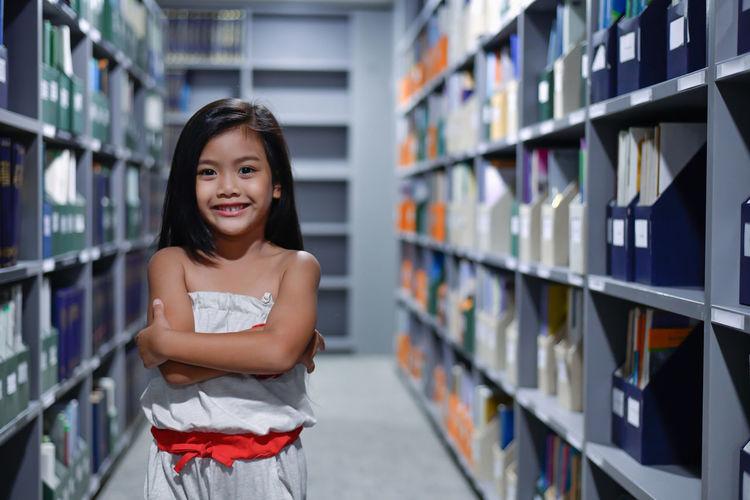 Smiling Girl Standing Amidst Bookshelves In Library