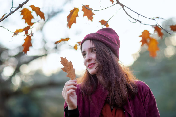 Portrait of young woman with ice cream in park during autumn