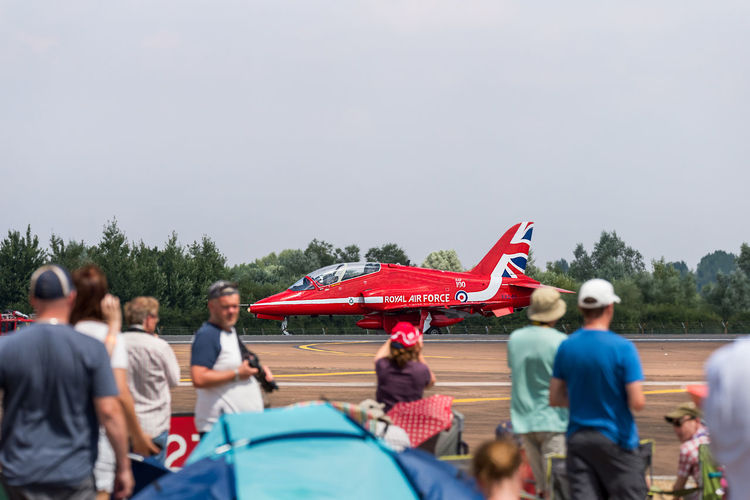 A single Red Arrow BAE systems Hawk T1 of the Royal Air Force taxiing on the runway at RIAT Fairford 2018, UK, with spectators looking on. Fairford Flying Display Adult Crowd Day Flag Group Of People Large Group Of People Leisure Activity Lifestyles Men Mode Of Transportation Nature Pride Real People Red Arrows Spectator Taxiing Transportation