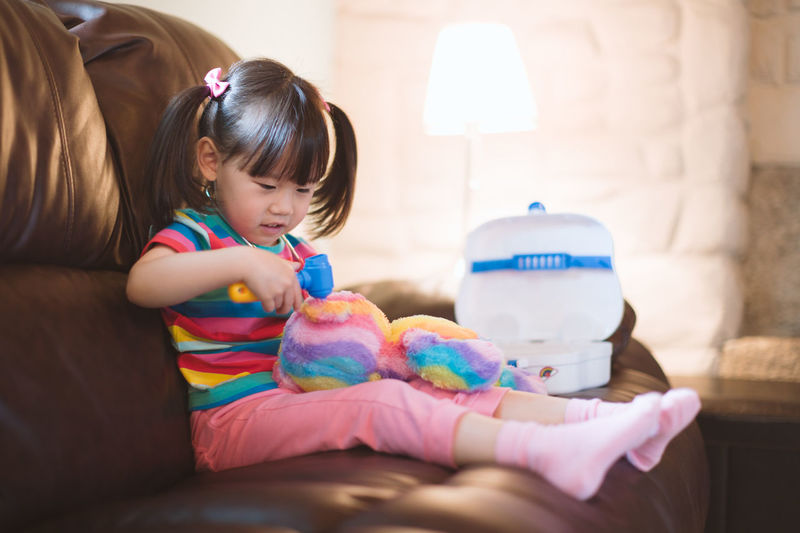 Young girl pretend play as doctor looking after her bear paient in the living room