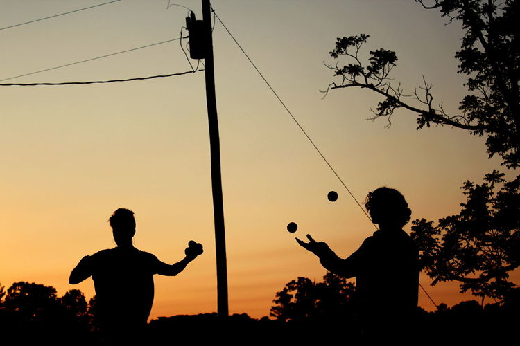 Silhouette People Juggling Balls Against Sky During Sunset