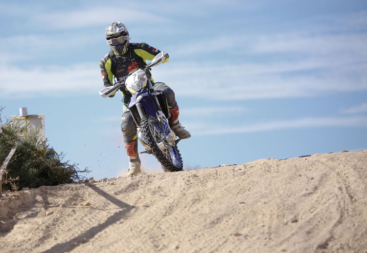 Low angle view of man riding motorcycle on sand