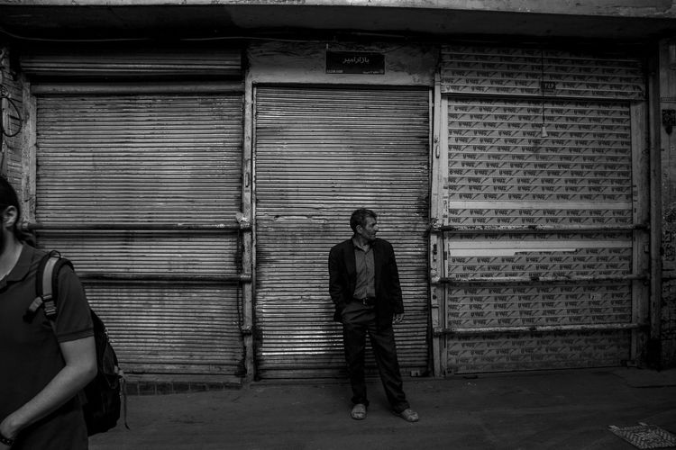 Full length of man standing on footpath against closed shutter