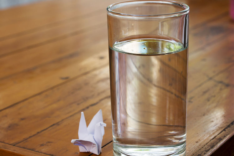 Paper crane by drinking water glass on wooden table
