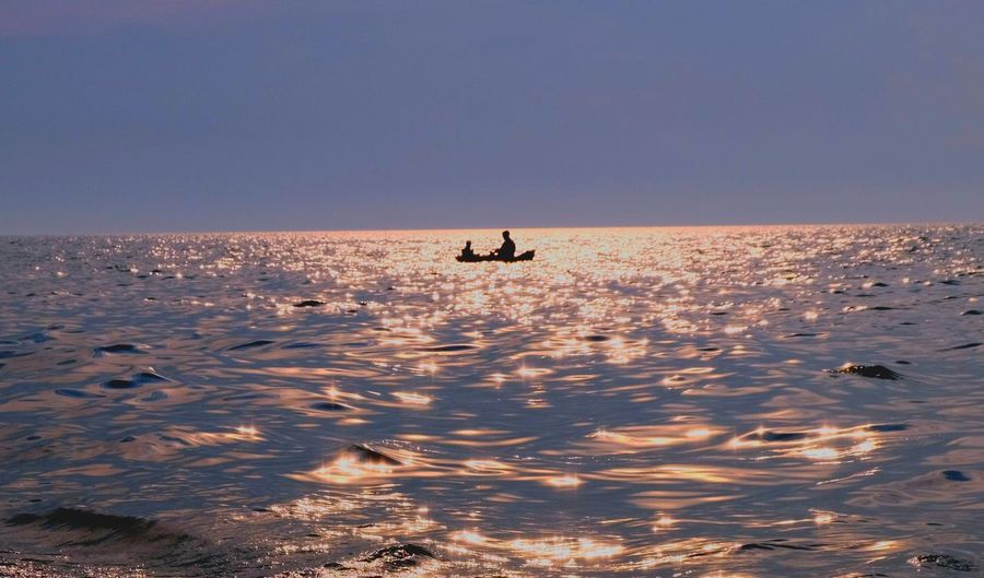 Silhouette person in a boat in sea against sky during sunset