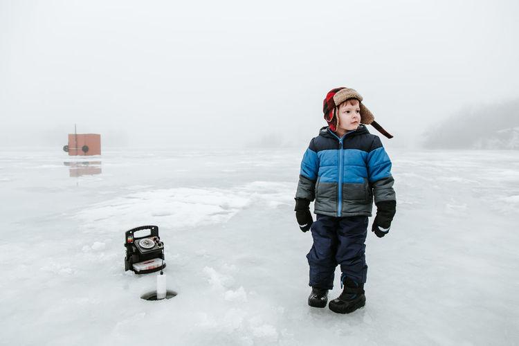Cute boy standing on frozen field