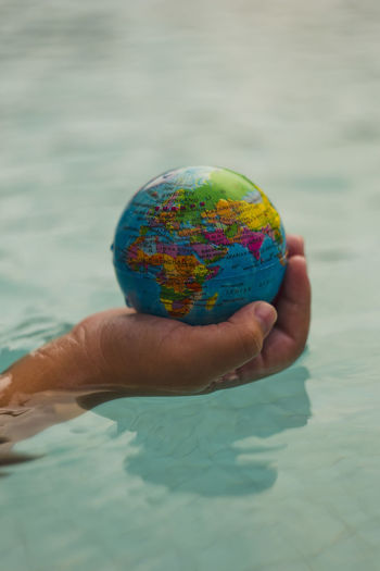Above close up looking down on hand holding the world over water Hand Holding Hands India Map Middle East Plant Power Africa Arab Cat Continent Ecology Energy Europe Planet Protection Sustainability Sustainable Sustainable Resources Water World