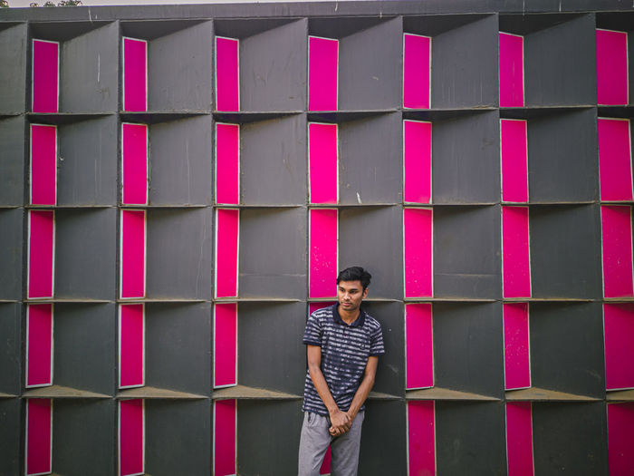 Full length of young man standing against pink wall