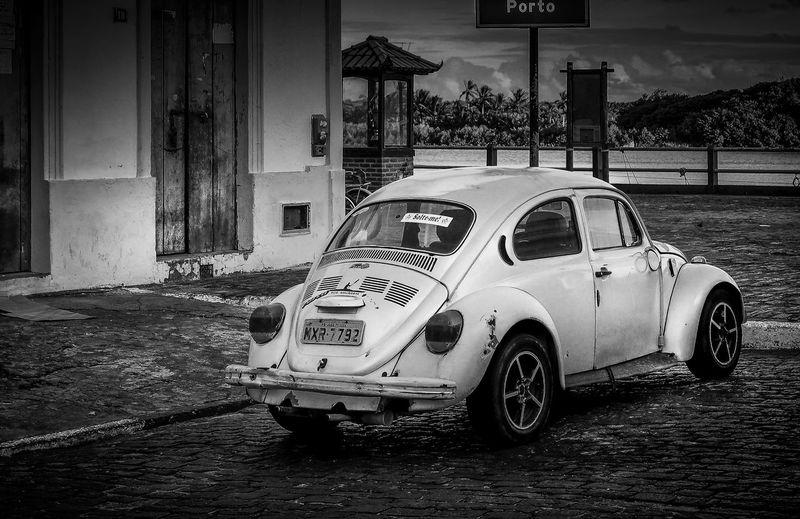 Vintage car on street by buildings in city