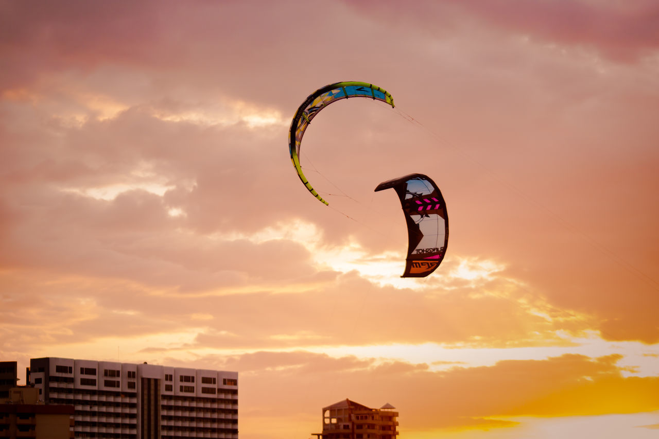 mid-air, extreme sports, sunset, exhilaration, adventure, leisure activity, sport, sky, parachute, real people, cloud - sky, nature, freedom, paragliding, outdoors, flying, low angle view, fun, beauty in nature, lifestyles, one person, motion, scenics, day, stunt