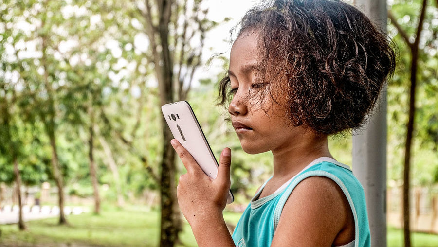 Side view of girl using mobile phone