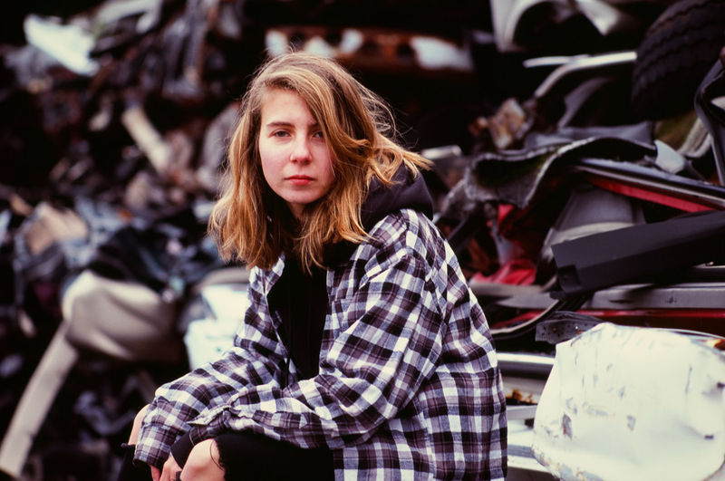 Young woman sitting by crushed cars in an auto salvage yard