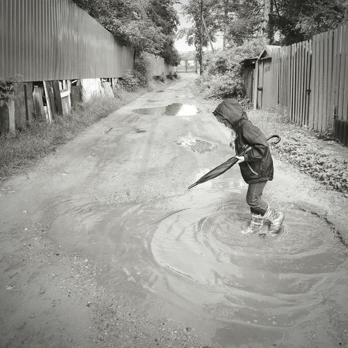 Side View Of Girl Jumping In Muddy Puddle
