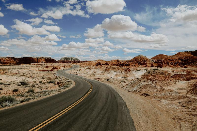Road passing through desert against sky
