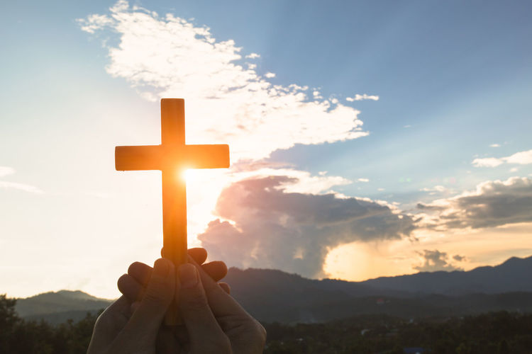 Cropped hand of person holding religious cross against sky during sunset
