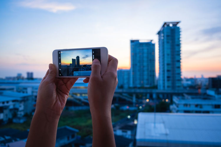 Cropped hands of woman photographing cityscape against sky during sunset