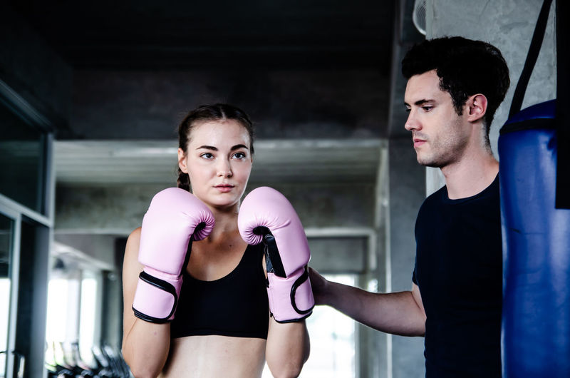 Man looking at woman while preparing for boxing in rink