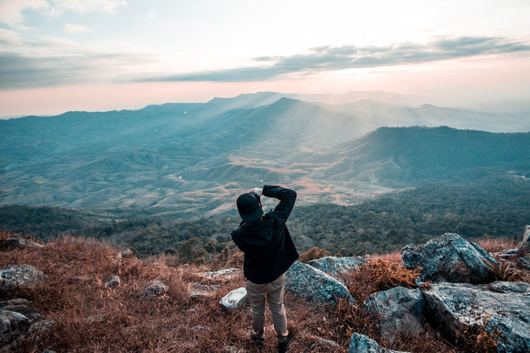 Rear View Of Man Photographing Through Camera While Standing On Mountain Against Sky During Sunset