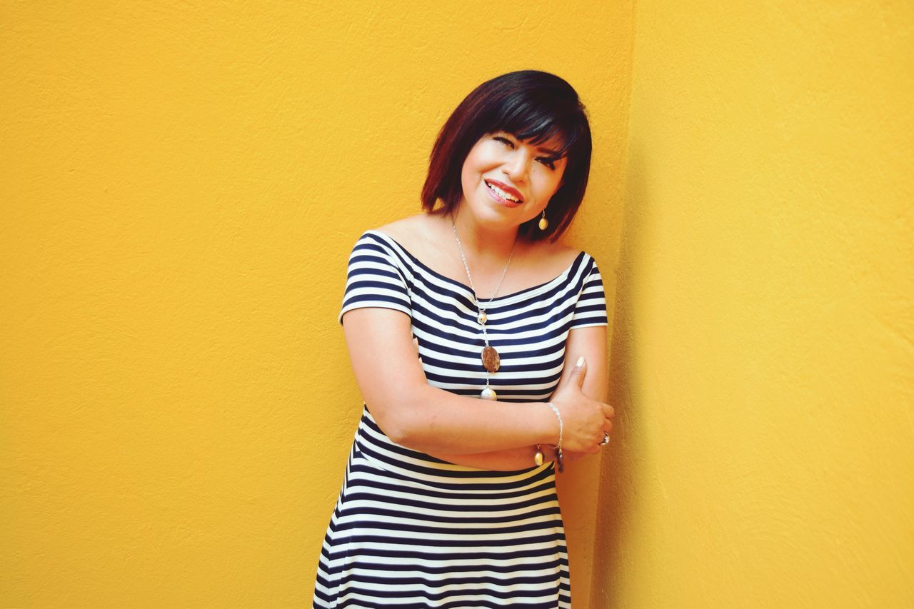 striped, casual clothing, young adult, wall - building feature, one person, three quarter length, young women, standing, front view, yellow, studio shot, yellow background, looking at camera, portrait, beautiful woman, real people, top - garment, lifestyles, smiling, white background, indoors, day, adult, people