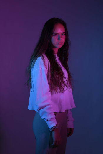 Portrait of teenage girl standing over purple background