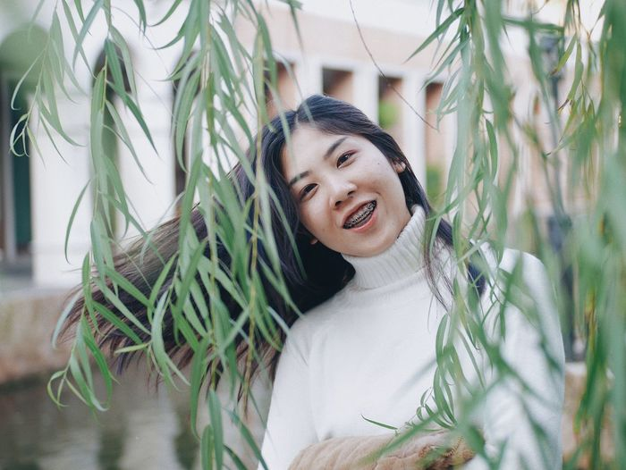 Portrait of smiling young woman standing by plants in park