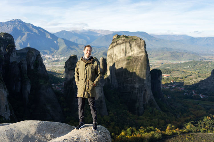 Man standing on rock against mountains
