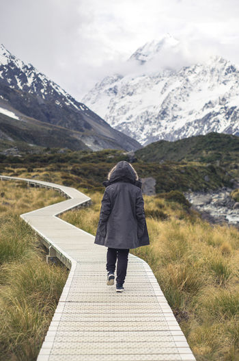 Rear View Of Woman Wearing Warm Clothing While Walking On Boardwalk Against Snowcapped Mountains