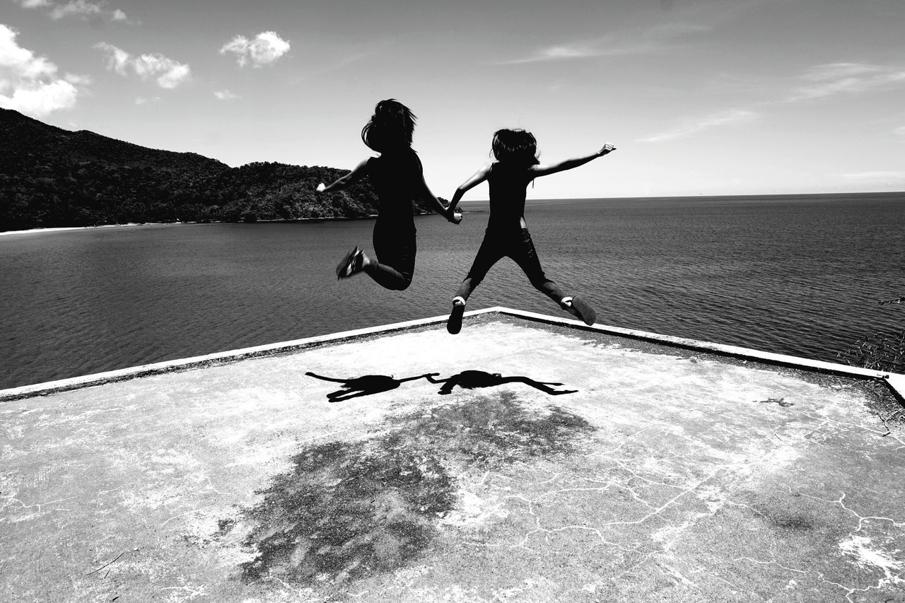 Full Length Rear View Of Female Friends Jumping At Pier By Sea Against Sky