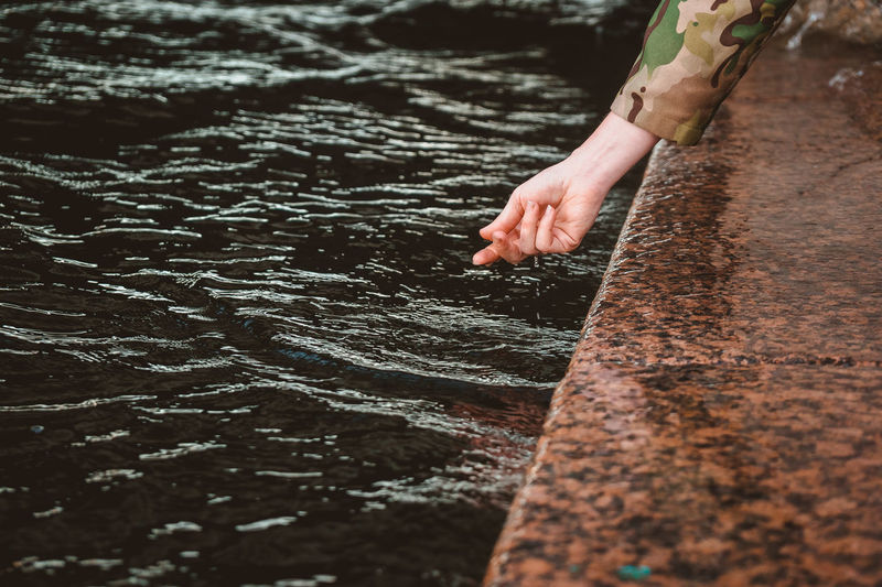 The girl's wet hand contact the water. touching the river with the palm of your hand while walking