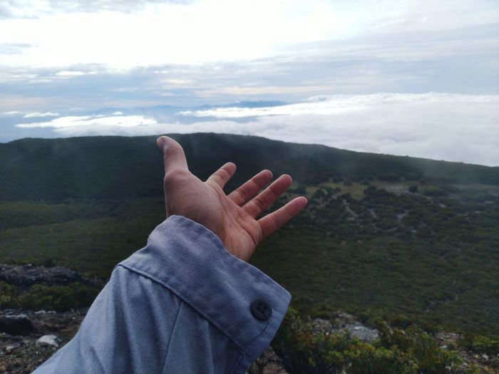 Midsection of person on mountain against sky