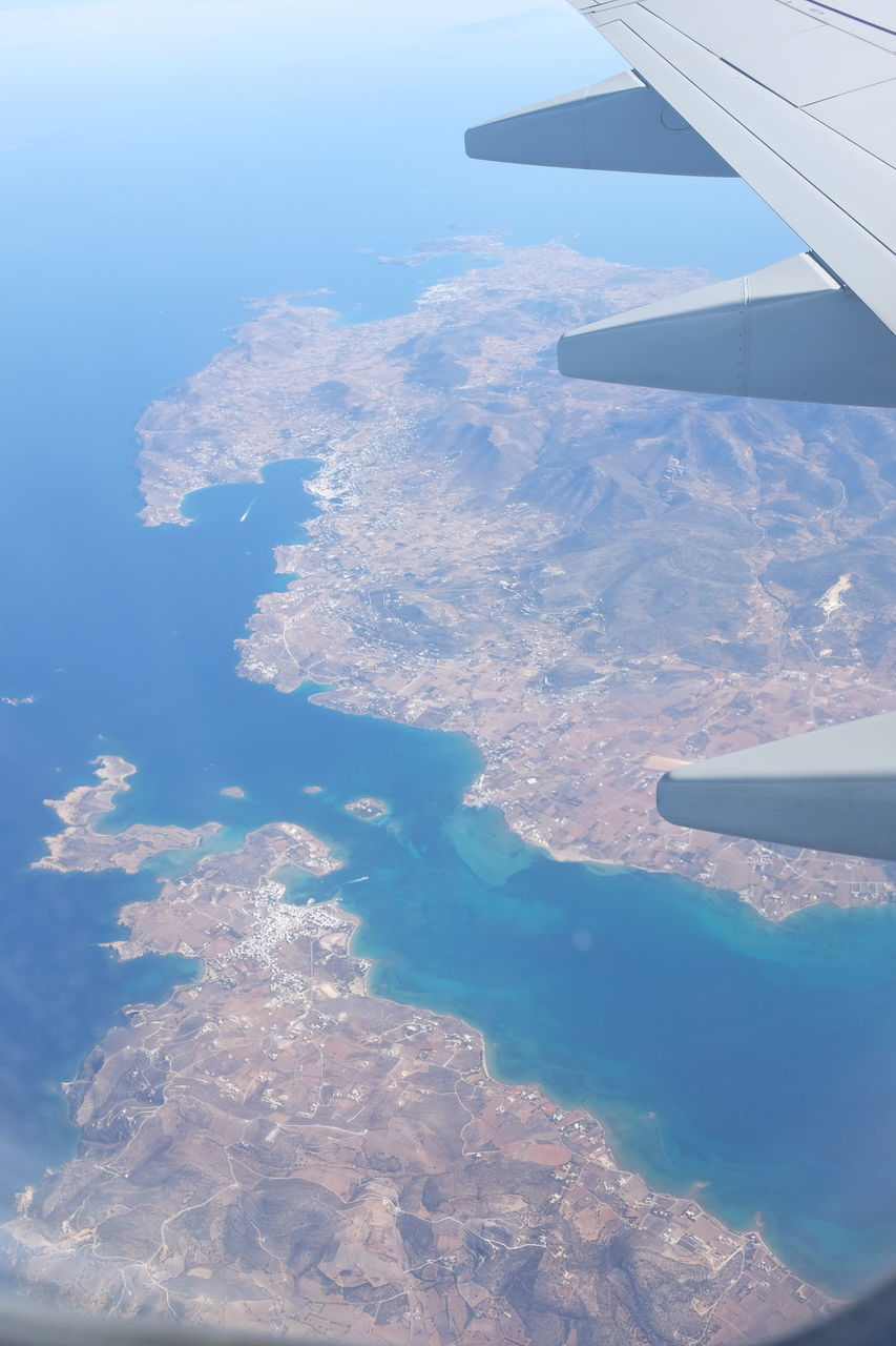 AERIAL VIEW OF AIRPLANE WING ABOVE LANDSCAPE
