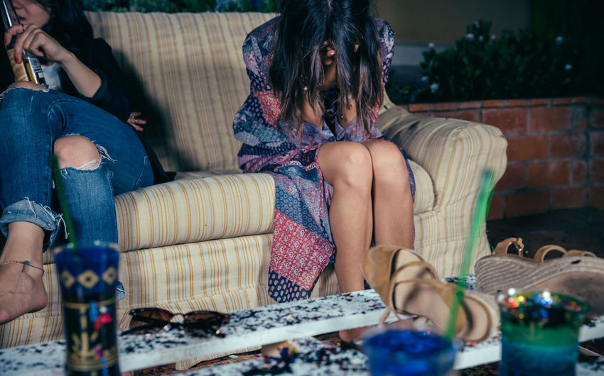 Drunk woman leaning on sofa during party in backyard at night