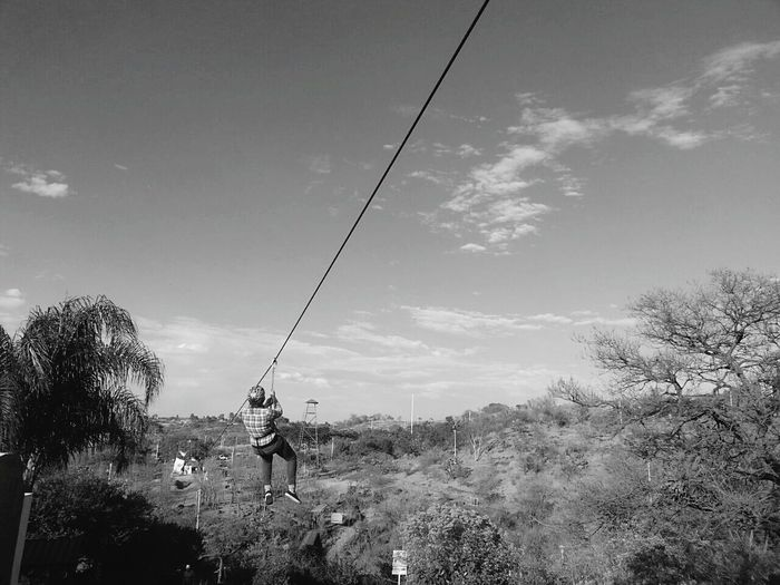 Full Length Rear View Of Person Zip Lining Over Landscape Against Sky