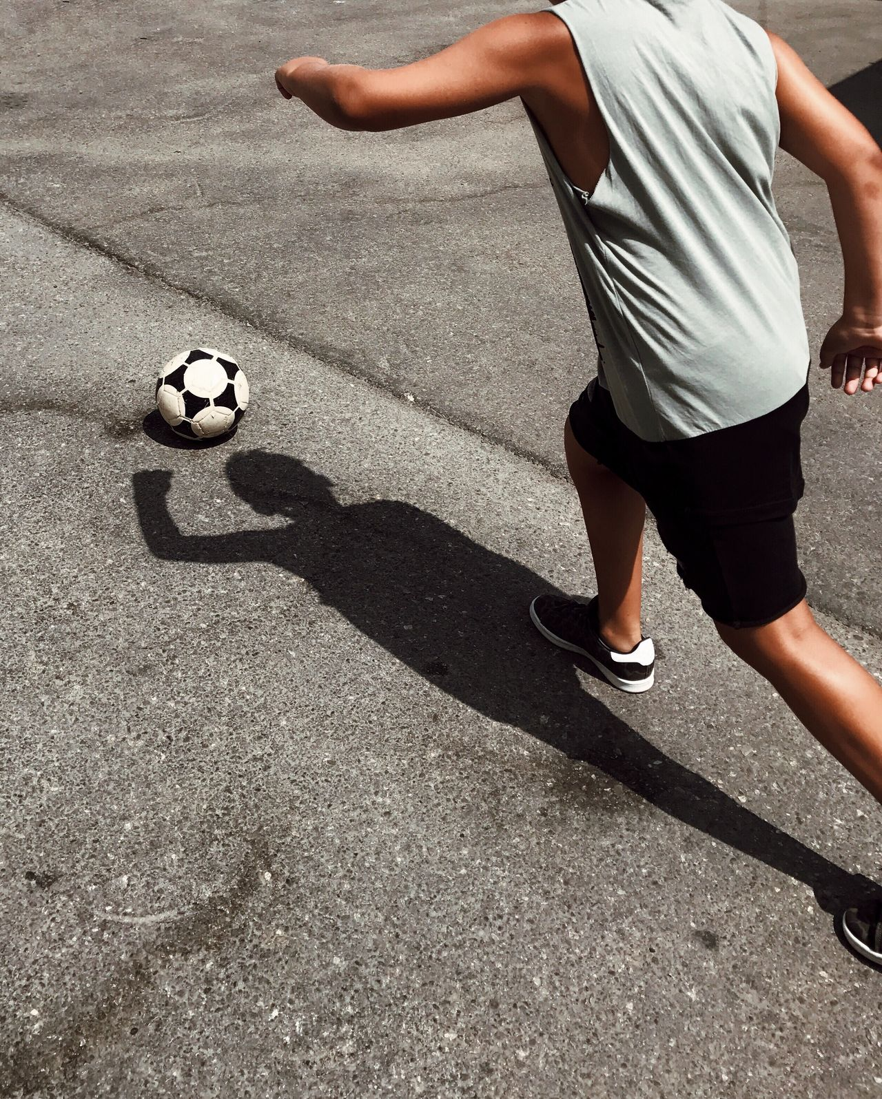 Low section of man playing soccer on street