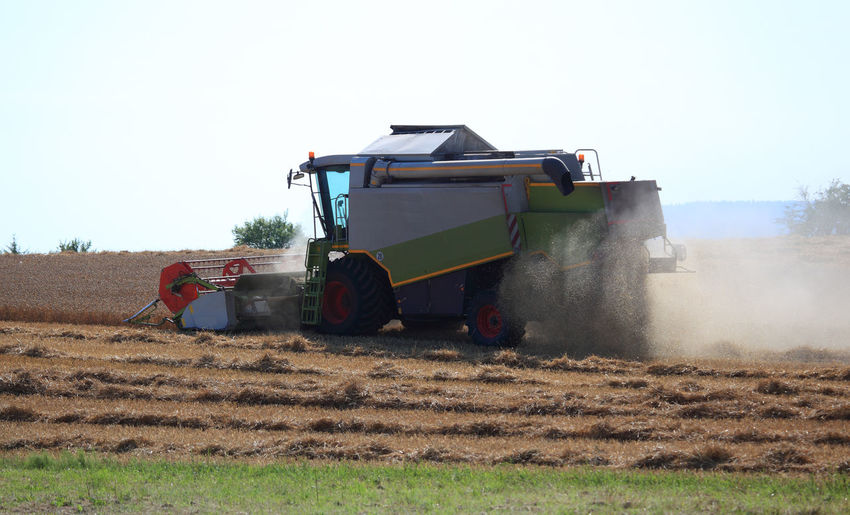 harvester during wheat harvest on a dry dusty field Agricultural Machinery Agriculture Clear Sky Combine Harvester Day Environment Farm Field Harvesting Land Land Vehicle Landscape Machinery Mode Of Transportation Nature No People Outdoors Plant Rural Scene Sky Tractor Transportation