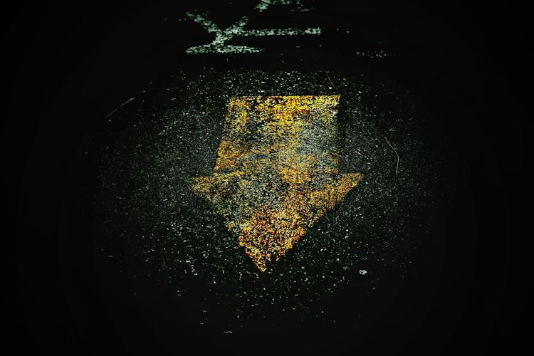 High Angle View Of Arrow Symbol On Road At Night
