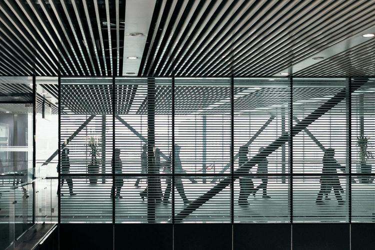 People walking in office seen from window