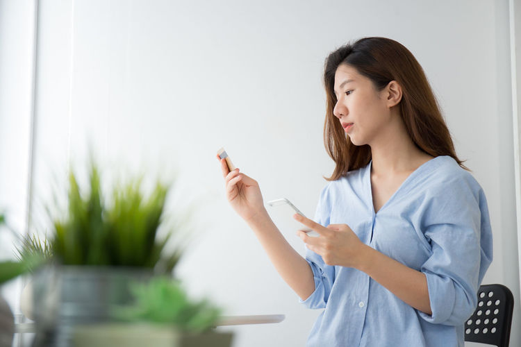 Woman doing online shopping through mobile phone at home