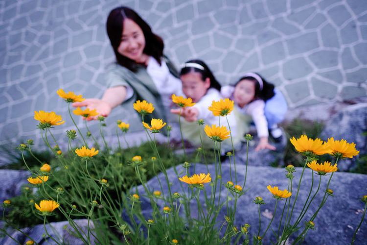 mother and daughers looking up to yellow wide flowers together Beauty In Nature Bonding Casual Clothing Child Childhood Daughter Day Flower Flower Head Fragility Freshness Girls Growth Happiness Leisure Activity Lifestyles Mom And Daughter Mother Nature Outdoors Petal Plant Togetherness Yellow