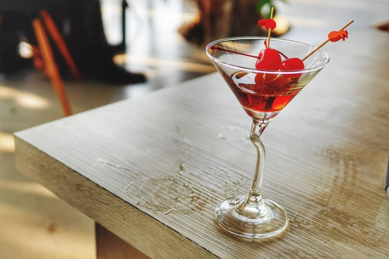 Close-up of red drink in martini on table