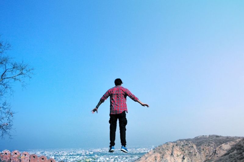 Full Length Rear View Of Man Jumping Against Clear Blue Sky