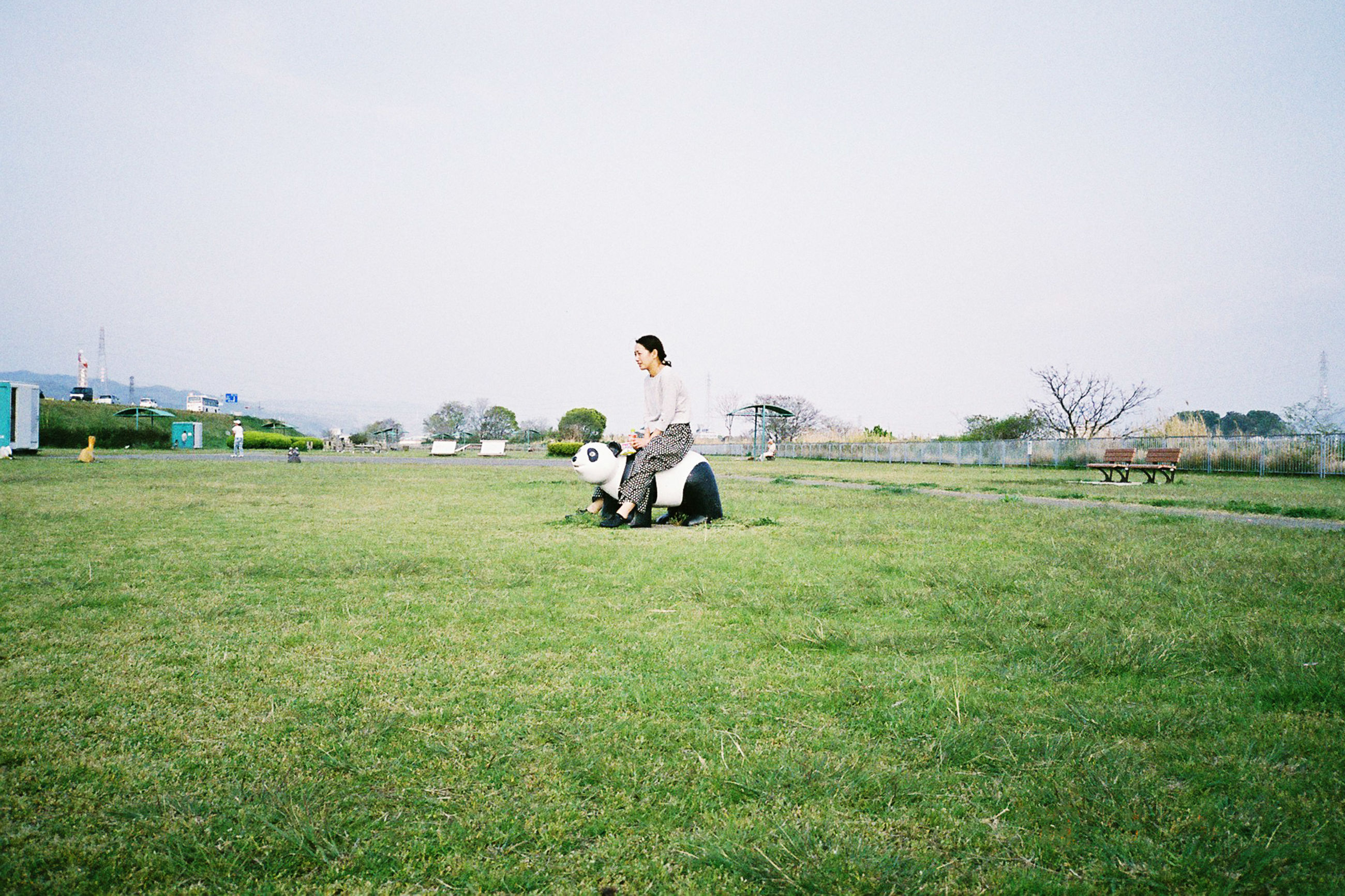 sitting, grass, sky, land, field, clear sky, real people, nature, full length, copy space, day, men, lifestyles, one person, plant, leisure activity, green color, environment, casual clothing, outdoors