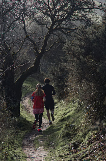 A young couple running down hill from the top of the Malvern Hills on a sunny but cold winter day Couple Exercise Hanging Out Malvern Hills Path Recreational Pursuit Running Sunny Day Winter The Great Outdoors - 2016 EyeEm Awards