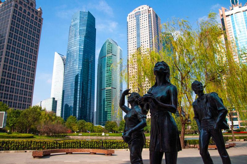 Statue of modern buildings against sky in city